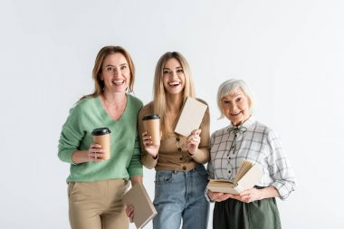 Three generation of cheerful women holding paper cups and books isolated on white stock vector