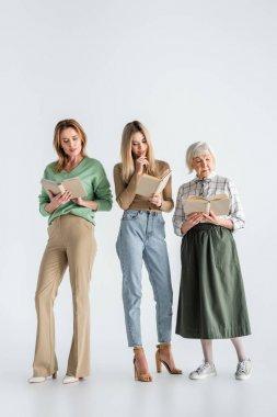 Full length of three generation of women reading books on white stock vector