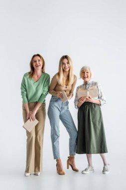 Full length of three generation of happy women holding books on white stock vector