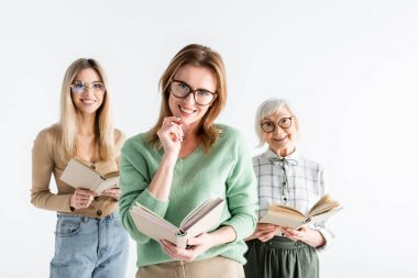 Three generation of smiling women in glasses reading books isolated on white stock vector