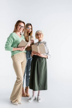 Full length of three generation of smiling women in glasses holding books on white stock vector