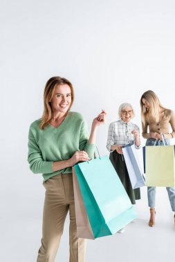 Happy woman with shopping bags near daughter and senior mother on blurred background stock vector