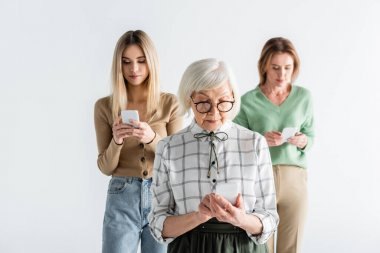 Senior woman in glasses using smartphone near daughter and granddaughter on blurred background stock vector