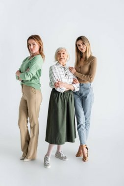 Full length of three generation of women looking at camera and posing on white stock vector