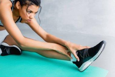 Genç Afrikalı Amerikalı sporcu evde spor paspası üzerinde esneme egzersizi yapıyor.