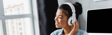 cheerful african freelancer woman listening music in wireless headphones at home, banner