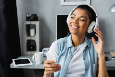 smiling african american freelancer listening music in wireless headphones while holding smartphone at home