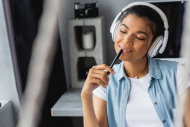 smiling, dreamy african american woman holding pen while listening music in wireless headphones, blurred foreground