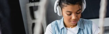 young african american woman listening music in wireless headphones at home, banner