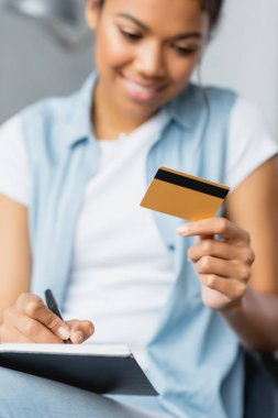 Smiling african american woman holding credit card and writing in notebook, blurred foreground stock vector