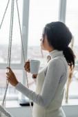 mladá africká americká žena dívá oknem, zatímco drží šálek teplého čaje