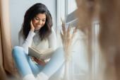 usmívající se africká americká žena čtení knihy v blízkosti okna doma na rozmazané popředí