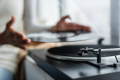 partial view of african american woman holding vinyl disc near record player, blurred background