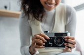 cropped view of smiling african american woman holding vintage photo camera, blurred background