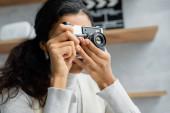 mladá africká americká žena fotografování na vintage foto kamery doma