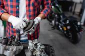 oříznutý pohled mechanika v kostkované košili a rukavicích držící ozubené kolo u demontované převodovky motocyklu