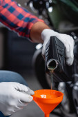 partial view of mechanic in gloves pouring motor oil from bottle into funnel