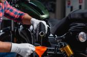 vágott kilátás szerelő öntés motorolaj tölcsér közelében motorkerékpár homályos háttér