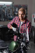 usmívající se mechanik při pohledu do kamery při diagnostice motocyklu v dílně