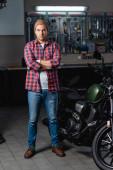 plný pohled mechanika v kostkované košili a džínách stojící se zkříženýma rukama v blízkosti motocyklu v dílně
