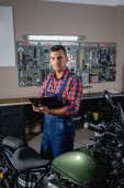 young technician in overalls looking at camera while standing with clipboard near motorcycle