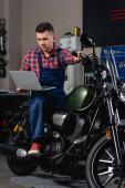 mladý mechanik v montérkách pomocí notebooku při sezení na motorce v dílně