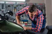 fiatal technikus kockás ingben vizsgálja motorkerékpár műhelyben