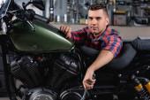 fiatal szerelő nézi kamera közelében motorkerékpár műhelyben