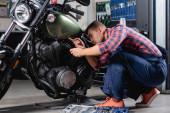 mechanik v montérkách s baterkou při diagnostice motocyklu