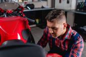 fiatal szerelő kockás ingben vizsgálja motorkerékpár műhelyben, elmosódott előtér