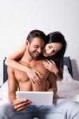 lächelnde brünette Frau umarmt hemdlosen Mann mit Tablette auf dem Bett