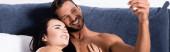 glückliches junges Paar macht Selfie auf dem Bett, Banner