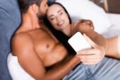 Hemdloser Mann küsst glückliche Frau auf Bett während Selfie auf verschwommenem Hintergrund
