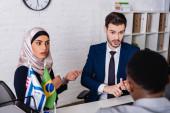 užaslá arabská podnikatelka gestikulující poblíž multikulturních obchodních partnerů, rozmazané popředí