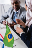 selective focus of arabian businessman holding cup of coffee near brazilian flag and african american business partner on blurred background