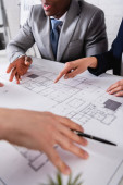 partial view of businesswoman pointing at blueprint during meeting with multicultural business partners, blurred foreground