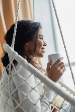 Side view of african american woman looking away while sitting in hanging chair with cup of warm tea stock vector