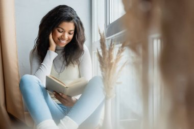 Smiling african american woman reading book near window at home on blurred foreground stock vector