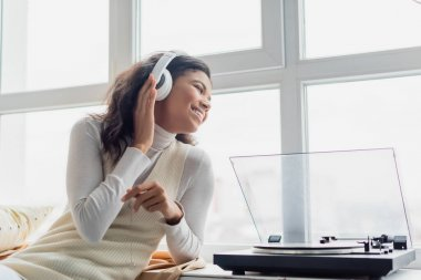 happy african american woman in wireless headphones looking through window near record player