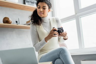 Young african american woman holding vintage photo camera while sitting near laptop on blurred foreground stock vector