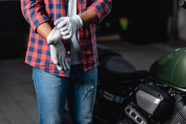 cropped view of mechanic in plaid shirt and jeans putting on gloves in workshop