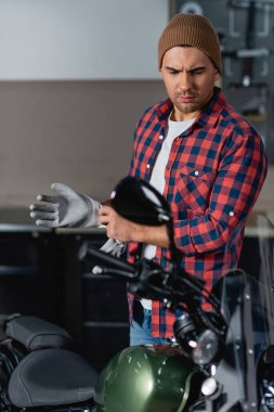 young mechanic in plaid shirt and beanie putting on work gloves near motorcycle, blurred foreground