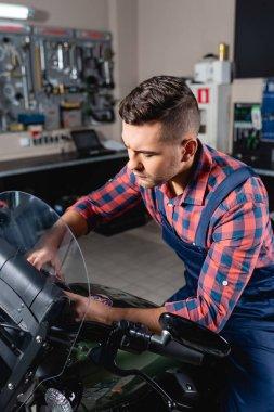 Young technician in overalls examining motorcycle in workshop stock vector