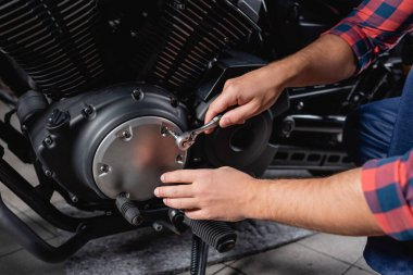Partial view of mechanic unscrewing cap of motorbike gearbox with socket wrench stock vector