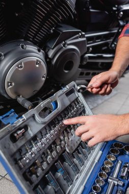 Cropped view of mechanic pointing with finger at bits for socket wrench in toolbox near motorbike gearbox stock vector