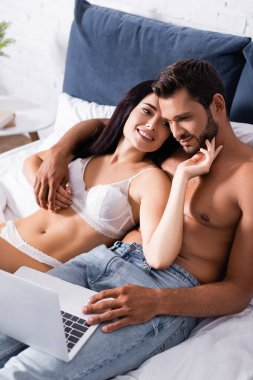 Smiling shirtless man looking at laptop while hugging woman in lingerie on bed stock vector