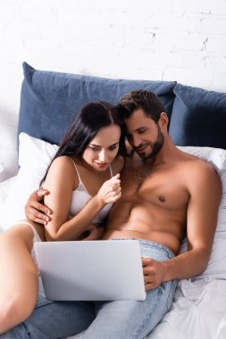Smiling sexy couple looking at laptop while lying on bed stock vector