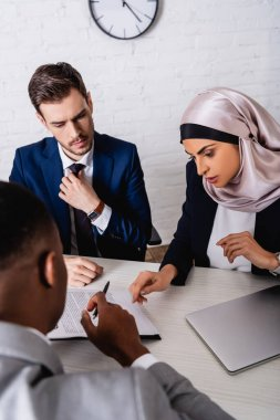 Arabian businesswoman pointing with finger at contract during meeting with african american partner and interpreter, blurred foreground stock vector