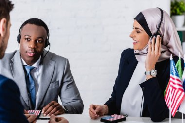 Smiling arabian and african american business partners in headsets near interpreter on blurred foreground stock vector