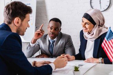 Cheerful arabian businesswoman looking at interpreter near african american businessman showing idea gesture stock vector